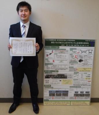 受賞した高木さんとポスター