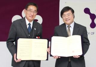 協定書を掲げる田辺市長と島田学長
