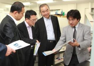 早川正幸理事(右から2人目)及び 山村英樹准教授(右)から研究内容に