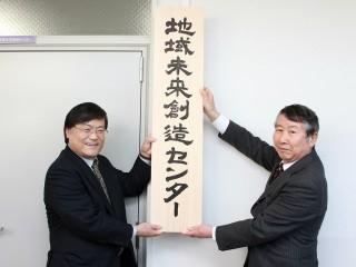 看板を掲げる島田学長(左)と北村眞一地域未来創造センター長(右)