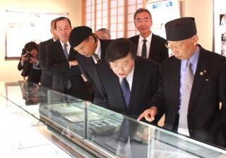 附属図書館で記念特別展をご覧になる大村先生(右)と島田学長ら