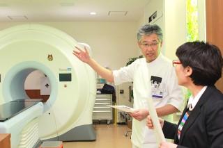 新病棟 放射線治療センターの視察坂本 肇診療放射線技師長(左)が国立大学で初めて導入されたトモセラピー装置について紹介