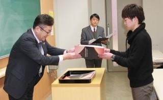 修了証を授与する樋川次長(左)と拝受する松山さん(右)