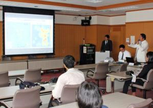 成果と計画を発表する鈴木センター長(右奥)