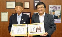 感謝状・記念品を手に 大村博士(左)と島田眞路学長(右)