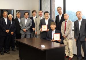 特別栄誉博士室にて記念撮影 大村博士・島田学長が持っている絵画は櫻井氏からの贈り物(右から2番目が櫻井氏)