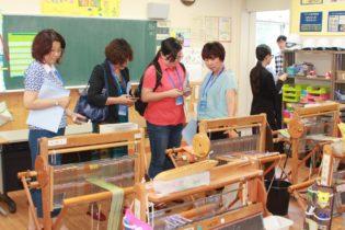 授業で使う織機に関心を示す代表団