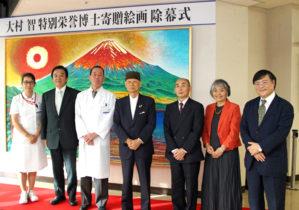 絵画の前で記念撮影(右から島田学長、櫻井夫人、櫻井氏、大村博士、藤井病院長、武田医学域長、佐藤看護部長)
