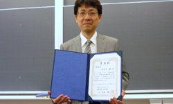 表彰状を掲げる喜多川准教授