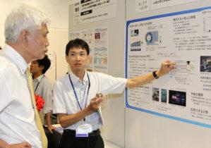 橋本教授(左)に電気推進ロケットを説明